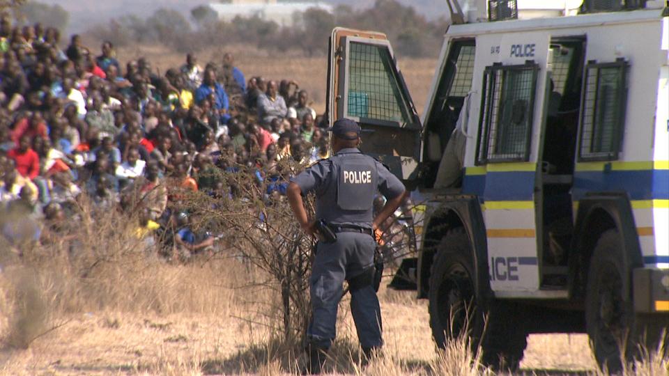 Police looking at striking mine workers on the koppie